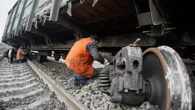 Railway workers examine a damaged wagon after an explosion in Yasinovataya town, Donetsk region, Ukraine, on Feb. 17, 2016.