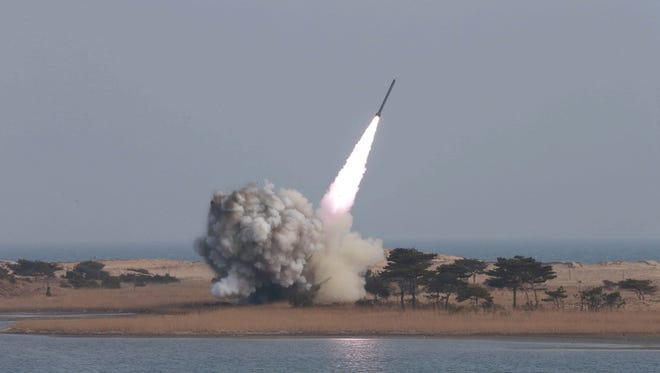 An undated photograph made available on March 4, 2016 by the North Korean news agency KCNA shows the test-firing of new-type large-caliber multiple launch rocket system.