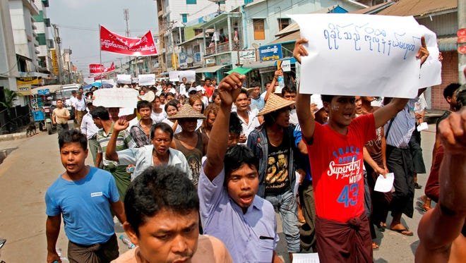 """Rakhine people hold placards reading """"Rakhine is not the colonial land"""" during a protest at Sittwe, Rakhine State, western Myanmar, on March 23, 2016."""
