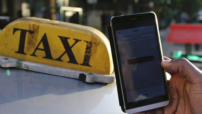 A Kenyan man holds his mobile phone displaying the Uber app next to a local taxi in the streets of Nairobi, Kenya, on March 24, 2016.