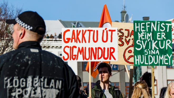 A man holds a sign in Icelandic reading 'Get out Sigmundur' as people gather during a protest on Austurvollur Square in front of the Icelandic Parliament in Reykjavic, Iceland on April 4, 2016, calling for the resignation of Prime Minister Sigmundur David Gunnlaugson.