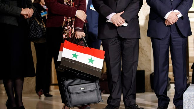 A member of the Syrian government holds a bag emblazoned with her country's flag during a press conference in Geneva, Switzerland, April 18, 2016.