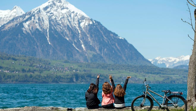 People enjoy the sunny weather in front of the Niesen mountain in Neuhaus near Interlaken, Switzerland, on May 5, 2016.