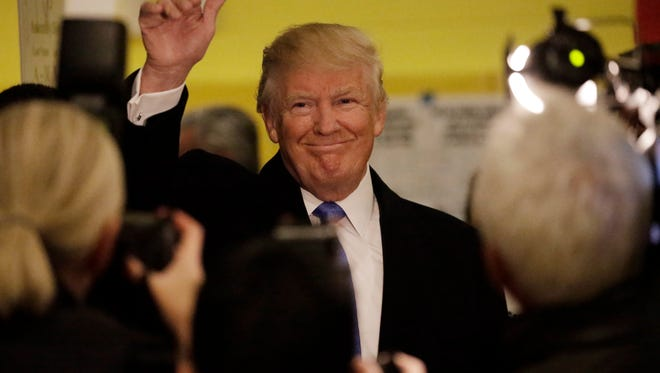 Republican presidential candidate Donald Trump waves to reporters after voting.