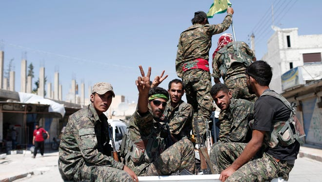 Members of Kurdish People Defense Units (YPG) flashing victory sign after coming from Syrian town of Raqqa, in Tel Abyad, Syria, in 2015. Reports state the Syrian Democratic Forces (SDF) announced on Nov. 6, 2016 that it had started a military campaign to liberate the northern Syrian city.