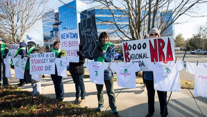 """Gun control advocates protest outside the National Rifle Association in Fairfax, Va., to call for """"sensible gun laws"""" on the fourth anniversary of the Sandy Hook massacre on Dec. 14, 2016."""