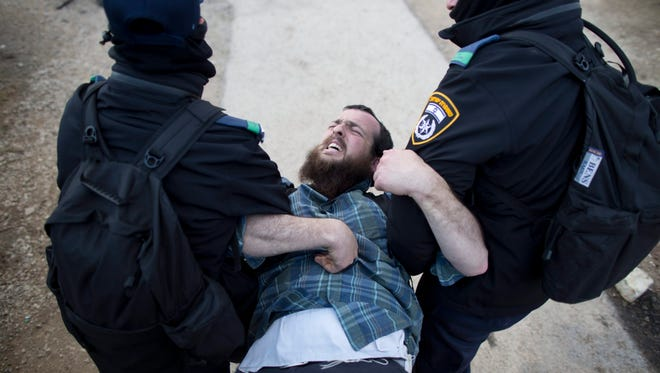 Israeli security forces arrest a settler during the evacuation of the illegal Jewish settlement of Amona, in the West Bank, on Feb. 1, 2017.