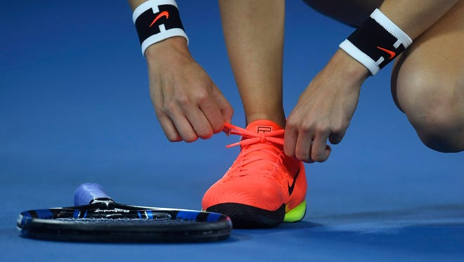 Eugenie Bouchard of Canada ties her shoes during her match against Coco Vandeweghe of the USA in round three of the Women's Singles at the Australian Open Grand Slam tennis tournament in Melbourne, Victoria, Australia, on Jan. 20, 2017.