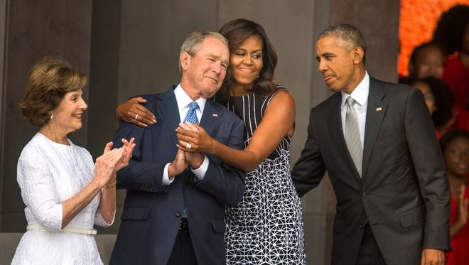 First Lady Michelle Obama hugs former President George W. Bush while President Barack Obama and former First Lady Laura Bush look on at the opening of the Smithsonian's National Museum of African American History and Culture in Washington, DC on Sept. 24, 2016.