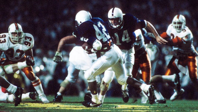 Penn State Nittany Lions quarterback John Shaffer (14) hands the ball off to running back D.J. Dozier (42) at Beaver Stadium during the 1987 Fiesta Bowl against the Miami Hurricanes. Penn State won the game 14-10.