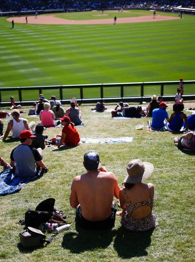 Baseball fans watch the game from the lawn as the Arizona Diamondbacks face off against the Colorado Rockies during spring training on March 27, 2016, at Salt River Fields at Talking Stick on the Salt River Pima Maricopa Indian Community.