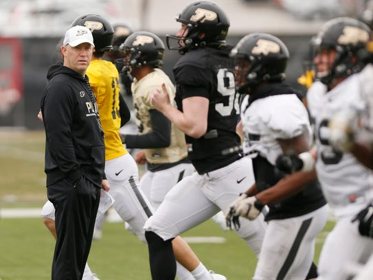 Head coach Jeff Brohm watches as players warm up for