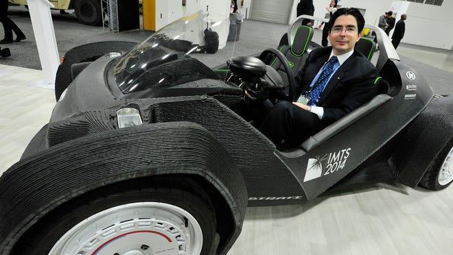 Jean Paul Capin Gally, CFO of Local Motors, sits in the first 3D-printed car at the North American International Auto Show at Cobo Center in Detroit on Monday.