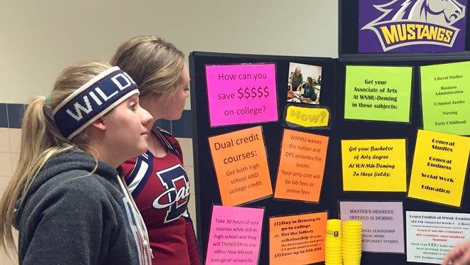 Deming High School students, at left, Taylor Rinehart and Ashton Treadwell look in on a poster board set up by Western New Mexico University-Deming Director Kenneth Leupold during a Wildcat basketball game at Deming High School. The students were interested in the programs and academic goals outlined at the Deming branch. Leupold said he occasionally sets up at the school to encourage students to seek out higher education after graduation.
