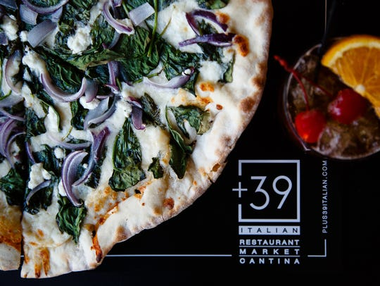 Pizza with caprino, onions and spinach is pictured
