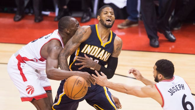 Indiana Pacers forward Paul George (13) gets fouled by Toronto Raptors center Bismack Biyombo  as Raptors guard Cory Joseph (6) looks on during the second half of Game 7  on Sunday, May 1, 2016, at Toronto.