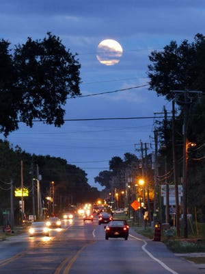 Tonight, weather permitting, is the night of a supermoon and lunar eclipse.  This view of moon trying to peak through the clouds was taken looking east over Olive Road Sunday evening.