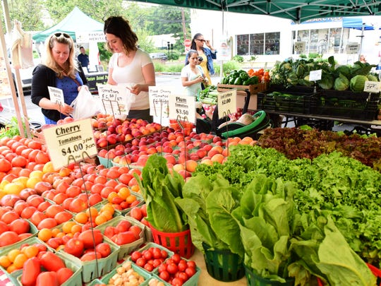 Shoppers at the Ort Farms tent. The weekly Farmer's Market in downtown Millburn brings families and restaurateurs together to buy farm fresh foods.