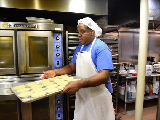 Tod Wilson brings pies to the oven for baking at Mr. Tod Pie Facotry in Englewood.