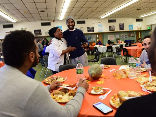 Chef Kookie Morrison hugs P.J. Roach, a former student at Thomas Jefferson Middle School in Teaneck, which opened its cafeteria to feed the community on Thanksgiving. Roach and his friends were playing football on the field behind the school when they found out there was food inside.