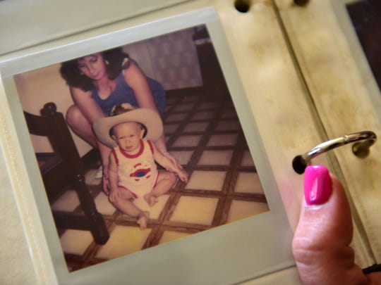 Amanda Zita looks through baby pictures of herself at her home in Wanaque.