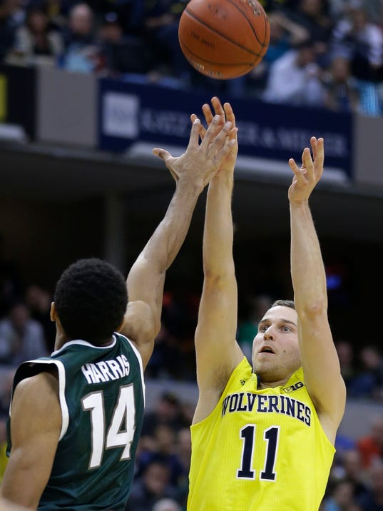 Michigan guard Nik Stauskas (11) shoots against Michigan State guard Gary Harris (14) in the second half of an NCAA college basketball game in the championship of the Big Ten Conference tournament on Sunday, March 16, 2014, in Indianapolis. (AP Photo/Michael Conroy)