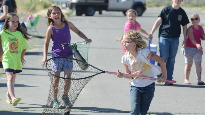 These young ladies happily carry their fish in nets to be measured at the conclusion of the 2015 Yerington Lions Club Kids Fishing Day.