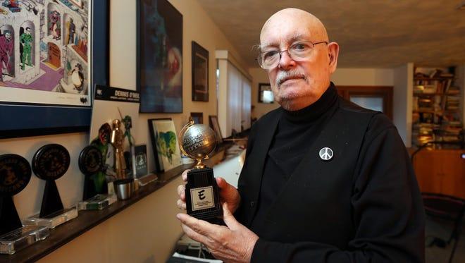Denny O'Neil at his Nyack home Feb. 25, 2016, displaying his Eisner Award.