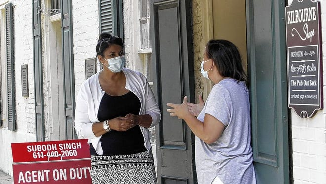 HER Realtors agent Linda Bolden (left) and administrator Martha Petrucelli chat outside their office in Worthington on July 9. Worthington recently joined a growing list of central Ohio cities requiring people to wear masks in public. Masks also have been required in Franklin County per a state mandate.