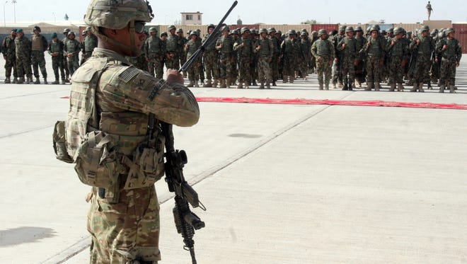 In this Sunday, July 24, 2016 photo, a U.S. military personal stands guard during a graduation ceremony in Lashkargah, capital of southern Helmand province, Afghanistan. An important district in Afghanistan's southern poppy-growing province of Helmand has fallen to Taliban control after heavy fighting that killed or wounded up to 20 police officers, an official said on Saturday.