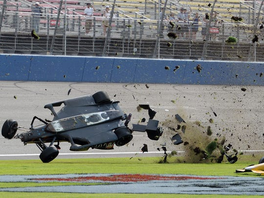 Ryan Briscoe flips through the infield grass in front of Ryan Hunter-Reay on Saturday June 27, 2015, during the IndyCar auto race at Auto Club Speedway in Fontana, Calif. (AP Photo/Will Lester)