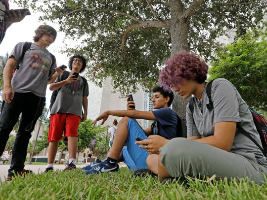 In this Tuesday, July 12, 2016 photo, Pokemon Go players