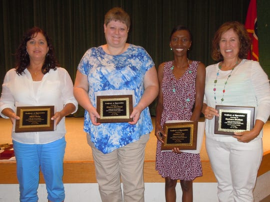 Receiving 20-year service awards were, from left, Niki
