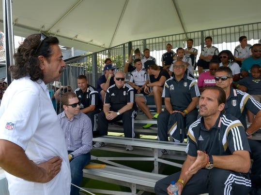 Jacksonville Jaguars owner Shahid Khan, left, talks to members of the Fulham FC soccer team during the Jaguars NFL football training camp in Jacksonville, Fla., Friday, July 25, 2014. Khan owns both teams. (AP Photo/Phelan M. Ebenhack)