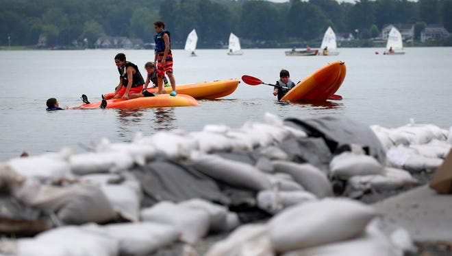 Campers from the Sodus Bay Junior Sailing Association enjoy calm waters in the bay as sand bags litter the shoreline after the lake flooding from earlier in the season.