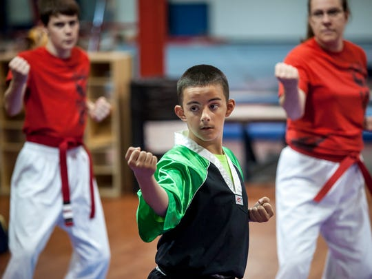 Leo Garcia, 12, practices a form along with other Fort Gratiot Tang Soo Do members during a training session Wednesday, June 28, 2016 at Kaleidoscope Gym in Kimball Township.