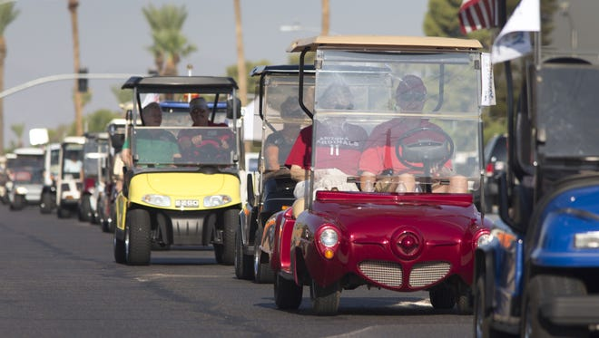 Denny Lockmon drove his red  golf cart with passenger Mary Ann Lemley in Sun City on Thursday along with over a hundred others to celebrate a 2014 law that allows such vehicles to drive in the shoulder of the road, and stay out of traffic's way, in some areas.