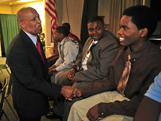 In this 2011 photo, Fred Bailey, left, shakes hands