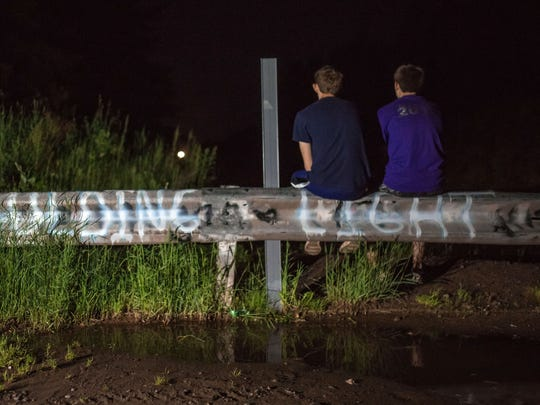 "Michael Hatfield (right), 16, and Alex Hendrickson, 16, both of Ironwood, sit on a road block off of Robbins Pond Road in Paulding, Mich. while watching the mysterious Paulding Light appear. Visitors have spray-painted the words ""Paulding Light"" so visitors know they've come to the right spot to see it."