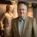 Republican Senator Mitch McConnell, senior United States Senator from Kentucky and majority leader of the Senate since January 3, 2015 poses near the stature of Henry Clay at the McConnell-Chao Archives at the University of Louisville.