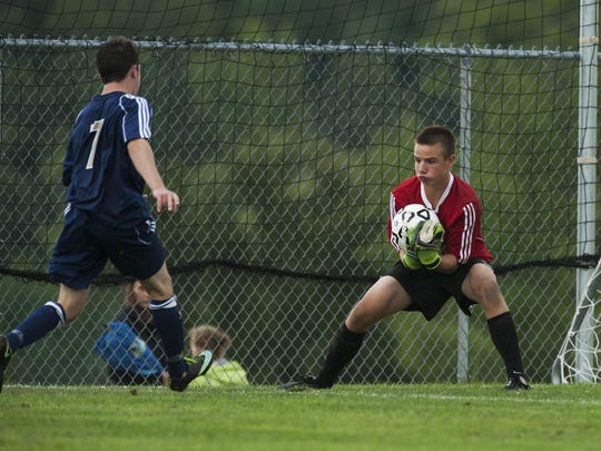CVU goalie Aidan Johnson (28) makes a save during the boys varsity soccer game between the Essex Hornets and the Champlain Valley Union Redhawks at CVU High School on Wednesday afternoon September 9, 2015.