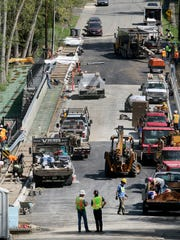 Redside Construction workers and contractors work on the new West Kingston Road Bridge on Thursday. The bridge is slated to open Monday.