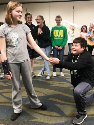 Shrek, played by St. Columban seventh-grader Nick Worpenberg, kneels before Daphne Laufersweiler, the fair yet feisty Princess Fiona.