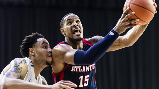 FAU forward Jailyn Ingram drives to the basket past Old Dominion forward Joseph Reece during FAU's 66-56 win Wednesday in the Conference USA men's basketball tournament.