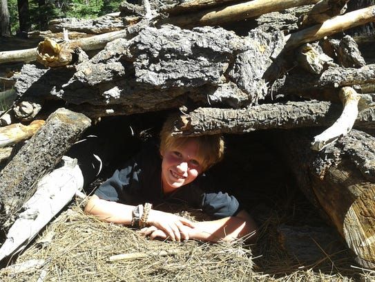 A child crawls under a shelter made during a summer