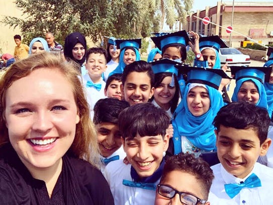 "Katelyn Jarvis in a ""selfie"" with graduating students in the ancient city of Babylon in Babil, Iraq."