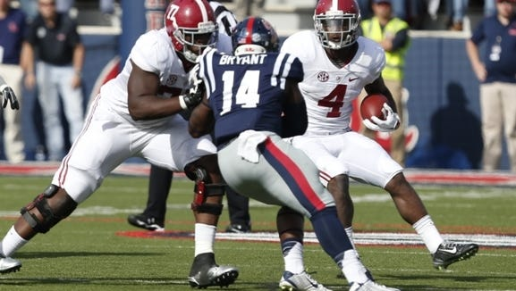 Alabama running back T.J. Yeldon (4) looks for a way around Mississippi linebacker Serderius Bryant (14) as a teammate blocks during the first half of an NCAA college football game in Oxford, Miss., Saturday, Oct. 4, 2014. No. 11 Mississippi won 23-17. (AP Photo/Rogelio V. Solis)