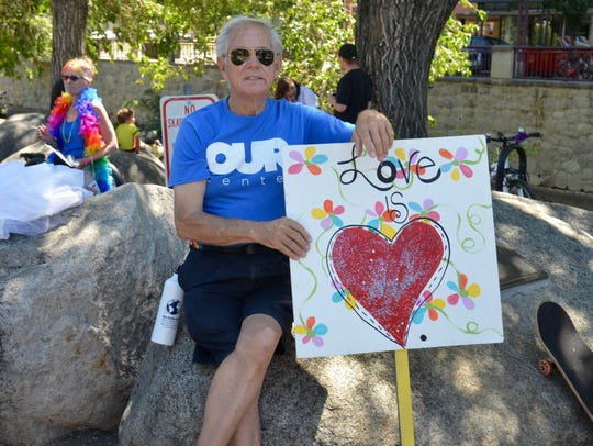 Warner Carr, a member of Our Center, holds a sign at