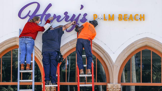 Workers from the sign making company RGE Associates and Bradford Electric work to install a halo-lit illuminated sign Tuesday on the exterior wall above the new Henry's Palm Beach restaurant at the former Testa's site. The restaurant will open at the mixed-use development called Via Flagler, an alfresco plaza project by the Frisbie Group and The Breakers.