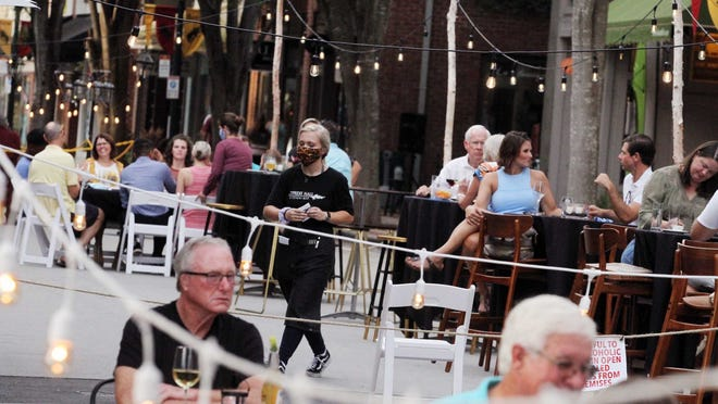 Restaurants and businesses serve patrons and diners at designated outdoor cafe areas in historic downtown New Bern, NC, August 21, 2020, as part of Phase 2 for reopening businesses.